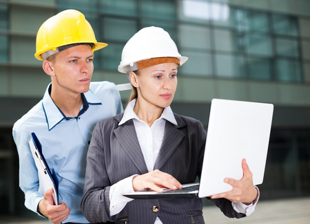 Woman designer and her partner are exploring project in laptop near the building. Standard-Bild - 123048241