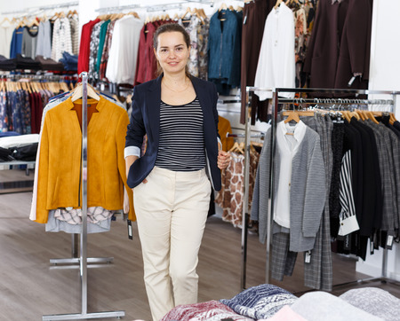 Woman in black jacket posing among racks with clothes in clothing shop Standard-Bild - 123048259