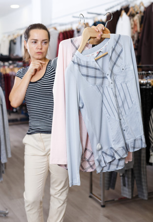 Young attractive woman choosing new clothes in clothing shop Standard-Bild - 123048260
