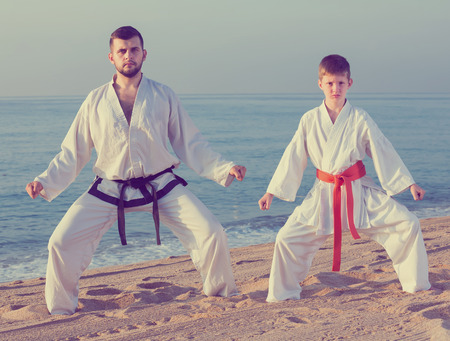 Man and boy practicing karate at ocean quay Standard-Bild - 123048267