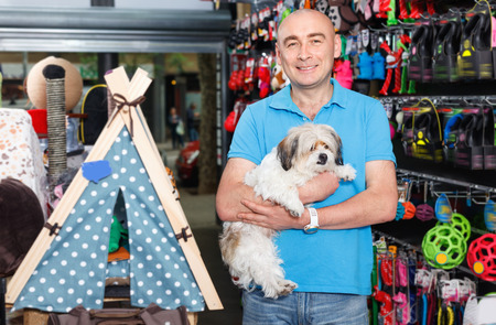 Portrait of cheerful positive young man  with small dog standing  in pet store Imagens