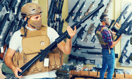 Young positive english  guys in military equipment with rifle in airsoft shop Archivio Fotografico