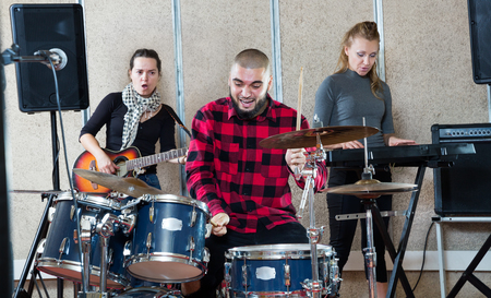 Rehearsal of music group. Rock band with emotional male drummer playing in a recording studio Standard-Bild - 123048302