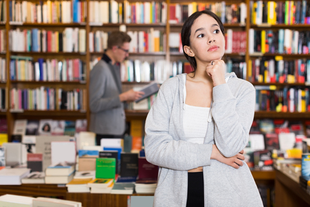 Thoughtful female student standing in library on background with colorful bookshelves