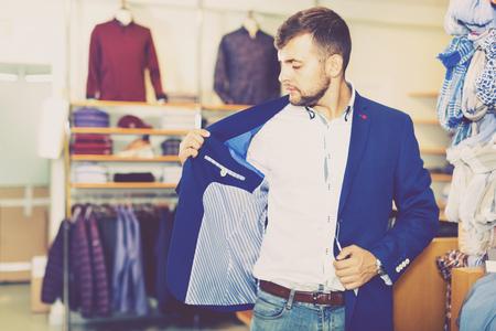 Happy  positive smiling handsome adult guy  choosing modern jacket in men store Standard-Bild - 123049222