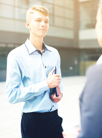 Businessman is talking with partner before signing contract outdoors near office. Standard-Bild - 123049231