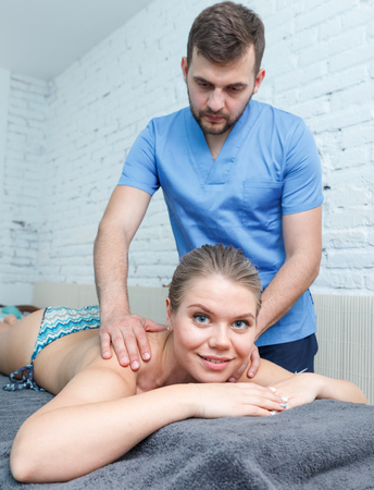 Portrait of young woman enjoying relaxing massage by professional masseur Standard-Bild - 123049227