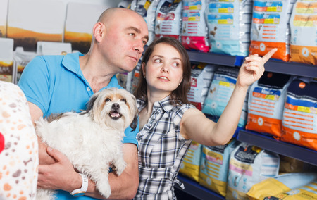 Portrait of cheerful woman and man with dog selecting vet food in petshop Standard-Bild - 123049232
