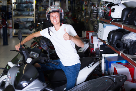 Smiling purchaser sitting on the motorbike in the shop with helmet Standard-Bild - 123049238