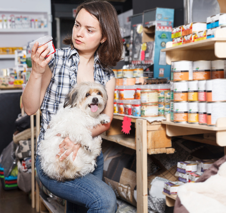 Portrait of woman with small dog  selecting  preserves  in pet shop Standard-Bild - 123049239
