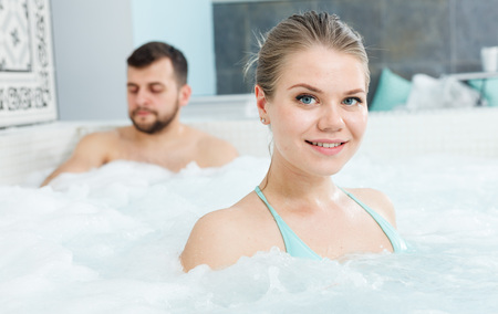 Attractive girl enjoying vacation in luxury spa resort, relaxing in hot tub Stock Photo