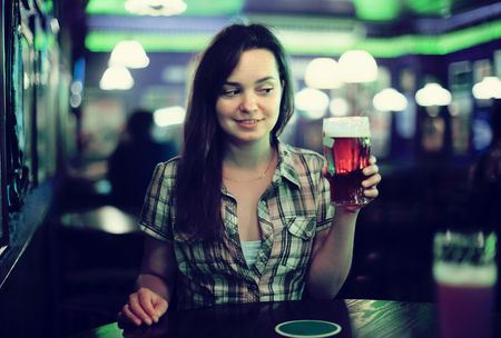 Young sexy girl sits in bar with beer glass Standard-Bild - 123049243