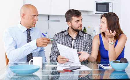Unhappy young couple signing financial agreement with social worker at home Standard-Bild - 123049249