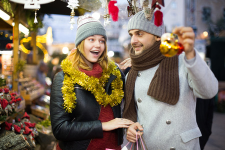 Positive young couple buying decoration at Christmas Fair outdoor Standard-Bild - 123049334