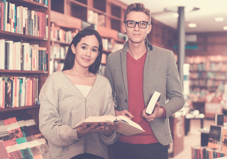 Young couple spending time together, choosing and discussing books in bookshop Standard-Bild - 123049337