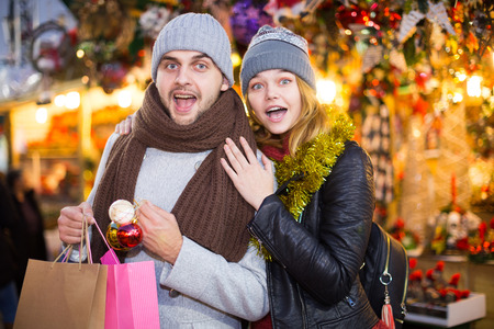 Portrait of joyful young couple delighted with purchases at  Christmas fair