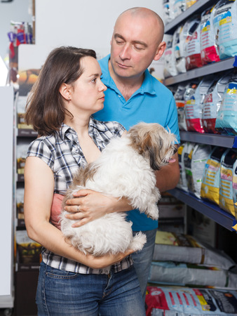 Portrait of cheerful family pair with dog selecting vet food in petshop
