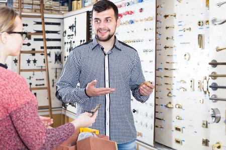 cheerful male seller assisting woman in choosing door handles in houseware shop Standard-Bild - 123049342