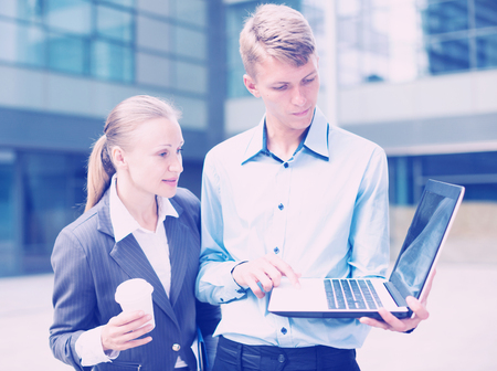 Businessman with his woman partner are looking project on laptop outdoors near the office. Standard-Bild - 123049343