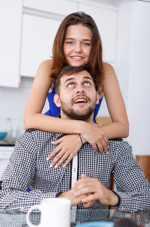 Portrait of smiling couple sitting at kitchen table and drinking tea Standard-Bild - 123049347
