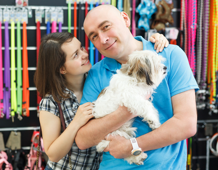 Portrait of smiling couple with dog in pet store, looking for new collars