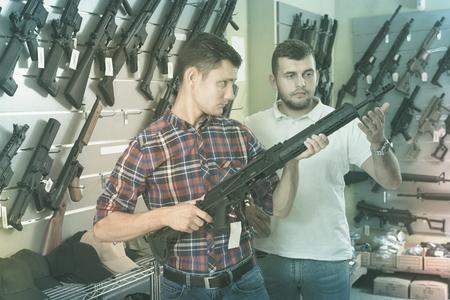 two male friends choosing air-powered gun in army market Standard-Bild - 123049352