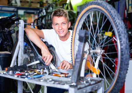 Satisfied  pleasant smiling man repairing bicycles with instruments indoors Standard-Bild - 123049353