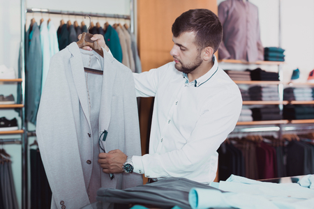 smiling man  choosing casual jacket in boutique Standard-Bild - 123049384