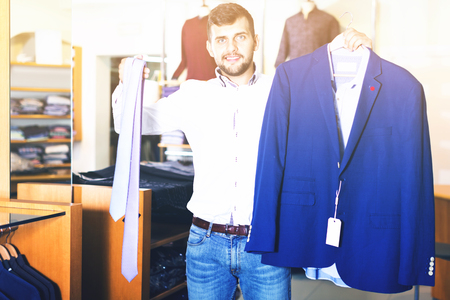 Positive  handsome adult guy  choosing modern jacket in men store Standard-Bild - 123049389