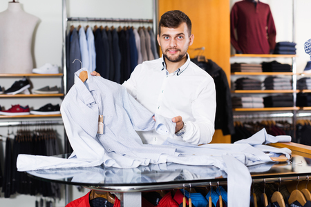 Happy male shopping assistant demonstration shirt in men outlet Standard-Bild - 123049391