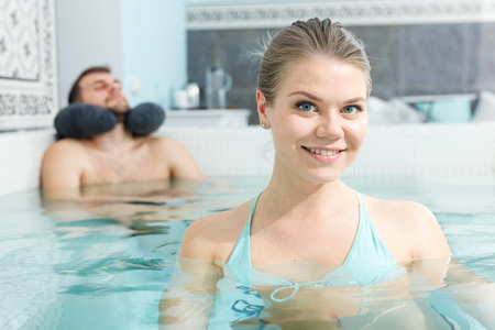 Young woman relaxing in jacuzzi during wellness weekend in spa center Standard-Bild - 123049396