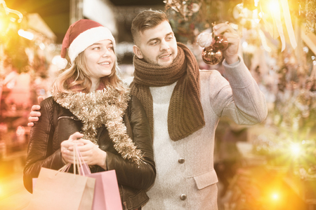 Portrait of joyful young couple in Christmas hat with Christmas toys at fair Standard-Bild - 123049401