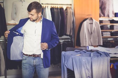 Ordinary male customer choosing jacket in men clothes shop