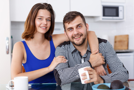 Portrait of young family couple sitting at kitchen table and drinking tea Standard-Bild - 123049421