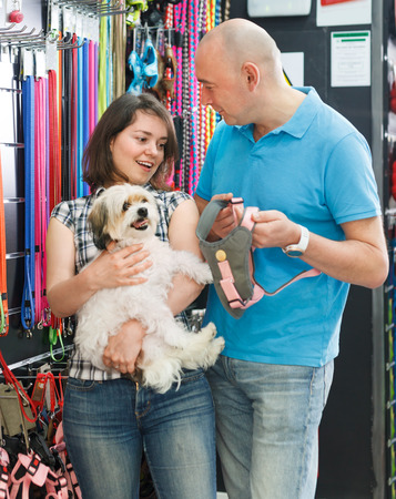 Smiling family couple with dog choosing for new leash in a pet shop. Focus on woman