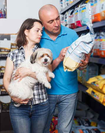 glad young couple with dog  buying dry food for dogs in pet shop Standard-Bild - 123049424