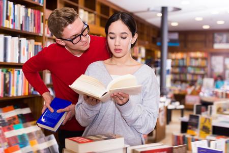 Buen estudiante mirando por encima del hombro de la niña eligiendo el libro en la biblioteca Foto de archivo