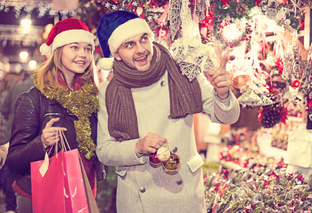 Smiling girl with boy in Christmas hat choosing decorations at market