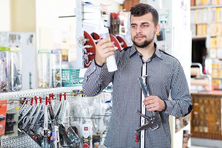 Adult man choosing new glue gun in houseware store