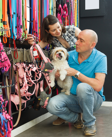 Positive family customers with dog looking for new collar  in pet store