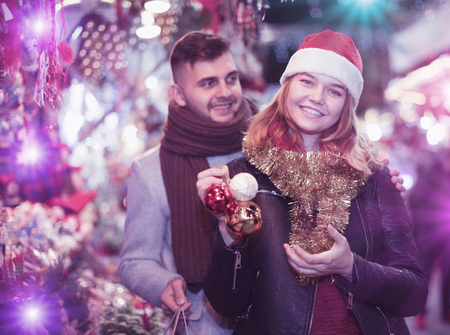 Smiling girl with boy in Christmas hat with purchases at market