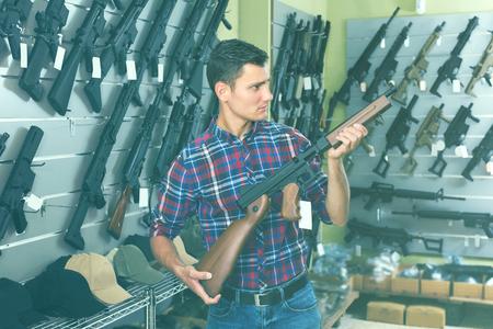 Male is choosing air-powered gun in army market. 版權商用圖片