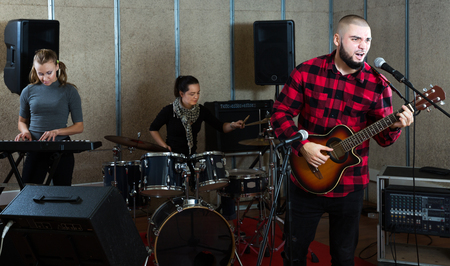 smiling young emotional guy with guitar rehearsing with female drummer and keyboardist before public performance Stock Photo