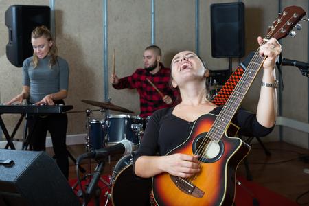 Repetitie van muziekband. Volwassen vrouwelijke gitarist en zangeres oefenen met bandleden in opnamestudio