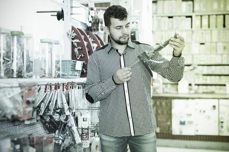 Man choosing new glue gun in houseware store
