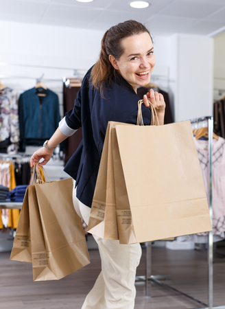 Young cheerful woman walking in clothing store and holding paper shopping bags in her hand
