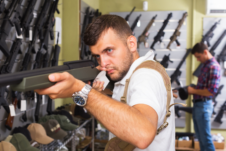 Positive young men buying air weapon in military store