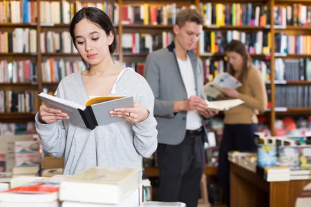 Beautiful girl reading interesting book in bookshop 写真素材