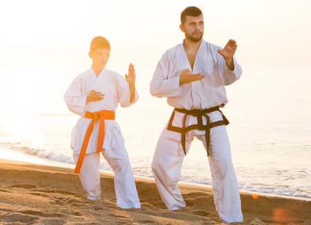 Teacher and boy doing karate poses at sunset sea shore