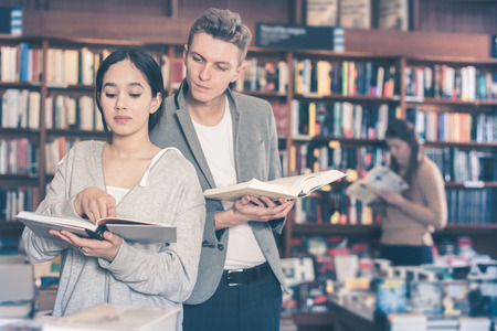 attractive young guy interested in book that girl reading in bookshop 写真素材
